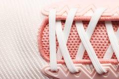 Kvinnarosa färger snör åt skor royaltyfria bilder
