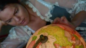 Kvinnasökande för en loppdestination på ett tappningjordklot stock video