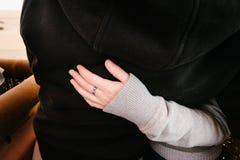 Kvinnas arm runt om partnern, ingen vigselring Arkivbild