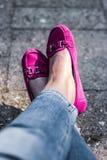 Kvinnas ben i rosa mockasin, sitta som är avkopplat arkivfoton