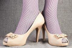 Kvinnas ben i strumpbyxor med beigea läderpip-tå skor Royaltyfri Bild