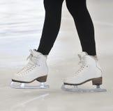 Kvinnas ben i vita isskridskor arkivfoto