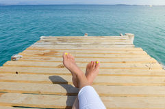 Kvinnas ben på en skeppsdocka, medan koppla av på sjösidan Royaltyfri Foto