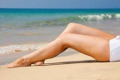 Kvinnas ben på stranden Arkivfoton