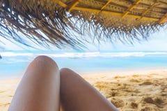 Kvinnas ben under parasollen p? den soliga tropiska stranden royaltyfri foto