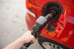 Kvinnas bensin för handpumpar in i den röda bilen arkivbild