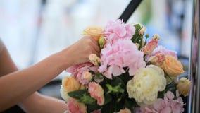 Kvinnas blomsterhandlares händer som gör buketten med rosa, orange och andra färger av olika blommor på tabellen för blomsterhand stock video