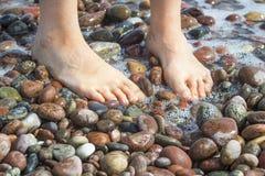 Kvinnas fot på stenar för en strand Royaltyfria Bilder