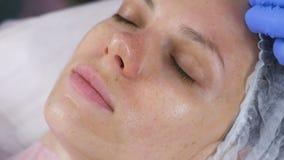 Kvinnas framsida med en genomskinlig maskering på hennes framsida Ansikts- behandlingar på kosmetologen arkivfilmer