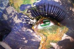 Kvinnas framsida med planetjordtextur och abkhazian flagga inom ögat Fotografering för Bildbyråer
