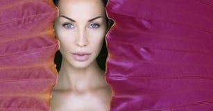 Kvinnas framsida som omges av den ultravioletta färgrika ramen Härlig kvinnaframsida med naturligt smink på ett tropiskt neonblad arkivbilder