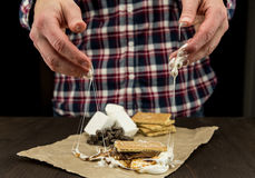 Kvinnas händer med den klibbiga smältta marshmallowen och Smore Arkivbild
