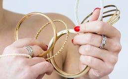 Kvinnas händer med guld- armband royaltyfria foton