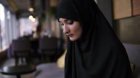 Kvinnas h?nder med smarta klockor som skriver p? en modern tunn b?rbar dator Koncentrerad ung muslim kvinna som arbetar p? modern lager videofilmer