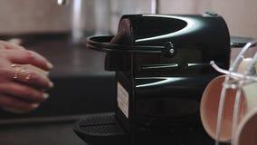 Kvinnas händer som gör nytt kaffe som ut går från en kaffeespressomaskin Framställning av espresso i keramisk kaffekopp stock video