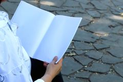 Kvinnas händer som rymmer anteckningsboken arkivfoto