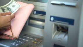 Kvinnas händer som sätter dollar i plånboken, kassa som återtas från ATM som reser arkivfoton