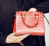 Kvinnas händer som sätter något i liten gullig trendig röd handväska Fotografering för Bildbyråer
