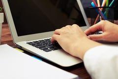 Kvinnas händer som skriver på tangentbordet på workspace Arkivbild