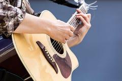 Kvinnas händer som spelar closeupen för akustisk gitarr arkivfoto