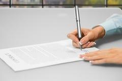Kvinnas händer som undertecknar kontorslegitimationshandlingar Arkivfoto