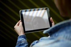 Kvinnas händer som upplysningsvis rymmer den digitala minnestavlan med den tomma skärmen för mallkopieringsutrymme eller innehåll Arkivfoton