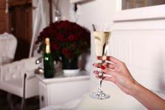 Kvinnas hållande exponeringsglas för hand av champagne i lyxigt sovrum Arkivbilder