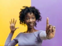 Kvinnas hand med fingret på blå bakgrund arkivbild