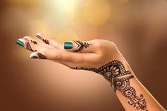 Kvinnas hand med mehnditatueringen royaltyfri fotografi
