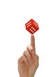 Kvinnas hand med peka för ett finger och röd tärning Royaltyfri Foto