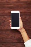 Kvinnas hand med smartphonen Arkivbild