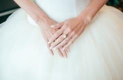 Kvinnas hand på den vita rena klänningen Arkivbild