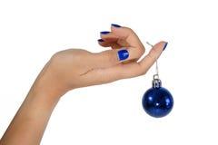 Kvinnas hand som rymmer en blå julstruntsak Arkivbilder