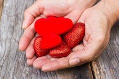 Kvinnas hand som rymmer en röd hjärtaform Arkivbild