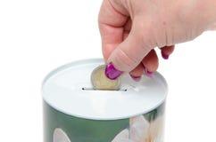 Kvinnas hand som sätter ett mynt i en moneybox Arkivfoto