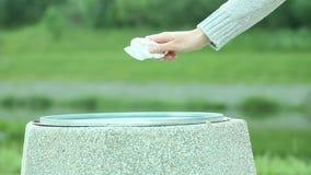 Kvinnas hand som ut kastar stycket av papper lager videofilmer