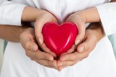 Kvinnas och mans händer som tillsammans rymmer röd hjärta Arkivbild