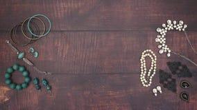 Kvinnas smycken på träbakgrunden arkivfilmer