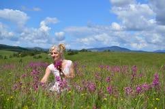Kvinnasammankomsten blommar på sommaräng Arkivbild