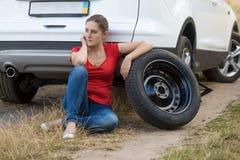Kvinnasammanträde bredvid bilen med det plana gummihjulet och väntande på hel Arkivfoto