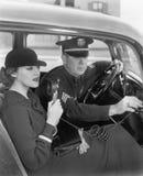 Kvinnasammanträde bredvid en polis i hans bil som rymmer en mikrofon i hennes hand (alla visade personer inte är längre uppehälle royaltyfri foto