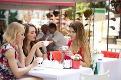 Kvinnasammanträde för tre lyckligt flickvänner på en tabell i sommaren c royaltyfri fotografi