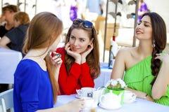 Kvinnasammanträde för tre lyckligt flickvänner på en tabell i sommaren c fotografering för bildbyråer