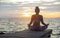 Kvinnasammanträde, i att meditera för yoga, poserar på havssidan mot beauti royaltyfri foto