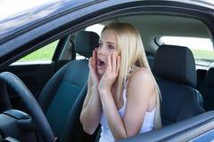 Kvinnasammanträde, i att skrika för bil arkivbild
