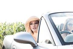 Kvinnasammanträde i cabriolet med den kvinnliga vännen på solig dag Royaltyfria Bilder