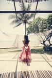 Kvinnasammanträde i en hängmatta vid stranden fotografering för bildbyråer