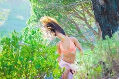Kvinnasammanträde i en skog som snärtar hennes hår med träd i bakgrunden arkivbilder