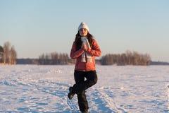 Kvinnasammanträde i en yogaposition på djupfryst sjösnö Arkivbilder
