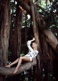 Kvinnasammanträde i enorma djungelträd med lianer i den vita tillfälliga klänningen royaltyfria foton